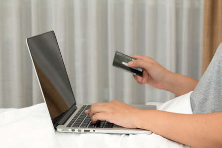 Online shopping concept : Close up of woman search goods with laptop and input credit number for payment on bed