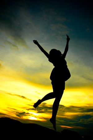 A happy woman jumping at sunset