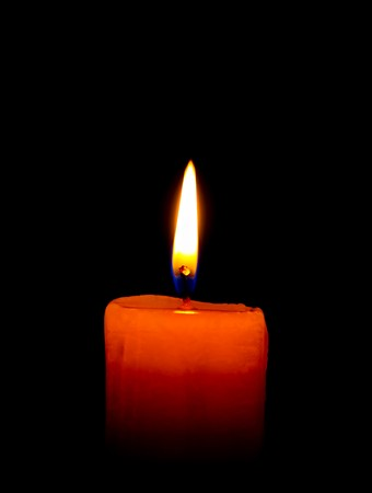 A single burning candle isolated on black
