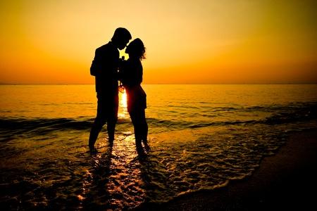 Romantic silhouette of wedding couple at sunset  Фото со стока