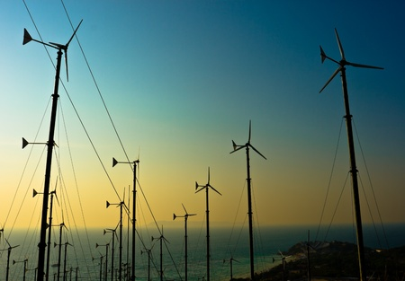 Wind turbines farm with a sunset,Pattaya Thailand Stock Photo