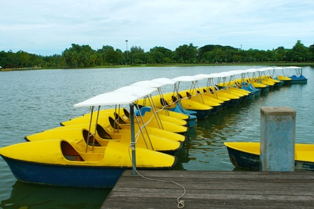 Yellow and  blue water cycling boats on still water in park ,Bankok ,Thailand.  photo