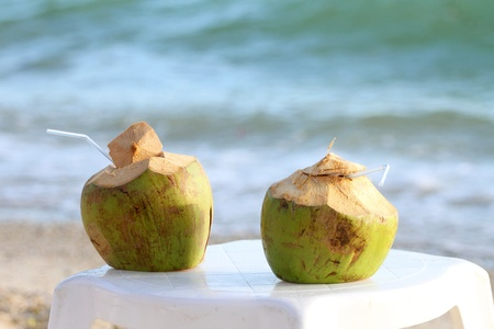Coconuts with drinking straw on the chair at the sea  photo