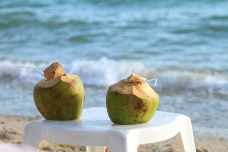Coconuts with drinking straw on the chair at the sea  Stock Photo - 11409277