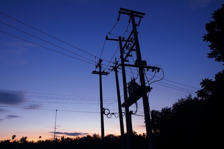 Transformers of an electrical post with powerlines at sunset.