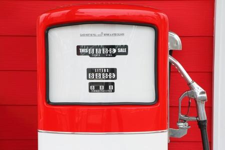 bomba de gasolina: Un vintage gasolina antigua bomba de gasolina sobre fondo rojo