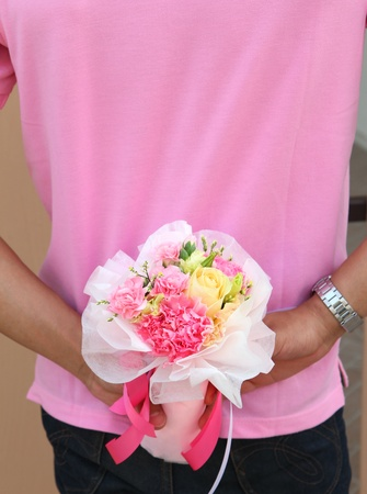 Beautiful bouquet hiding behide man back photo