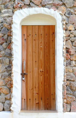 Wooden vintage door with stone wall to the  house photo