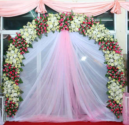 Beautiful backdrop flowers over pink and white fabric ready for wedding ceremony  Stock Photo