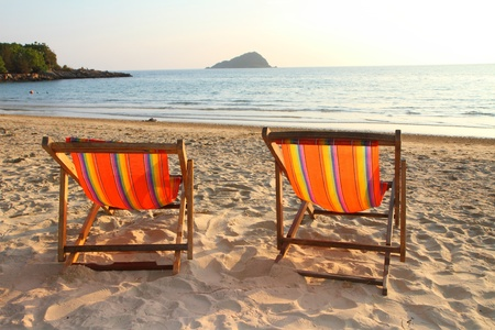 Twin deck chairs on the beach, at sunset photo
