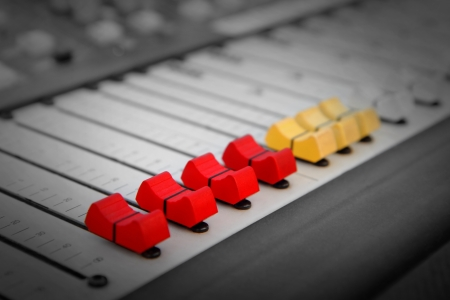 Close up of red and yellow audio sound mixer with buttons photo