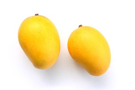 Ripe golden mangoes on white background