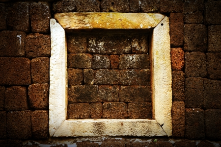 Ancient window in the old stone wall  photo