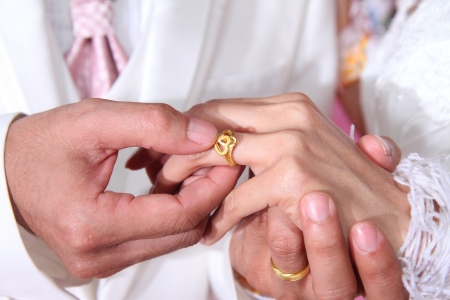 Groom putting a ring on bride s finger during wedding ceremony  photo