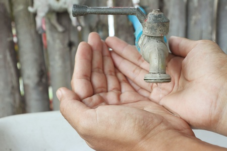 A man catches running water in his cupped hands outdoors