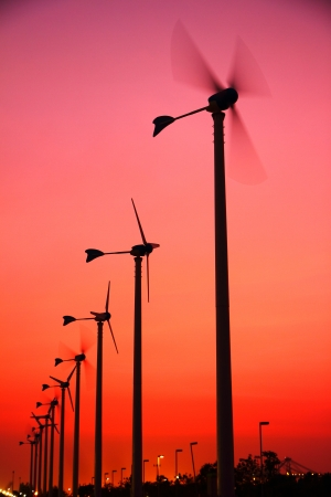 Clean energy wind turbine silhouettes are working at twilight  photo