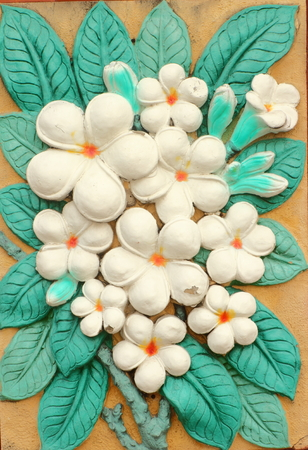 Low relief cement Thai style handcraft of plumeria or frangipani flowers  on wall  Stock Photo - 29272229