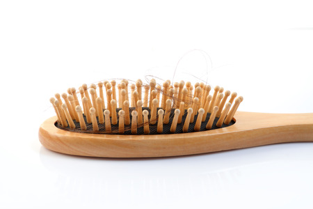 Wooden comb brush with lost hair, isolated on white background            photo