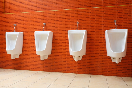White porcelain urinals in gents toilets photo