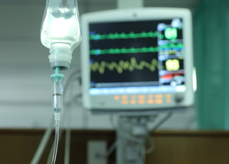 Drop of saline solution to help patient and medical monitors in a hospital. Stock Photo