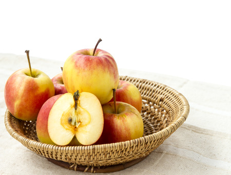 apple sack: Small gala apple and half in basket on sack over white background.