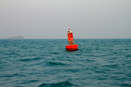 sea mark: Floating red navigational buoy on blue sea, Gulf of Thailand.