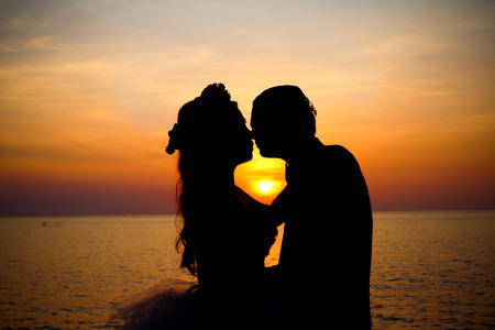 besos apasionados: Amor pareja bes�ndose rom�ntica escena silueta al atardecer.