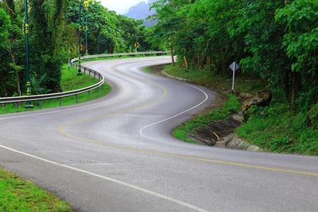 путешествие: Кривая путь асфальтовой дороги в зеленом виде. Фото со стока