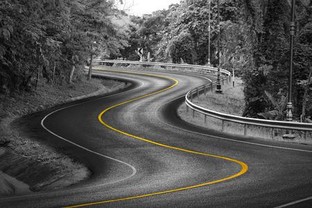 amarillo: Forma curva de blanco y negro de la carretera de asfalto en la naturaleza con la línea amarilla.