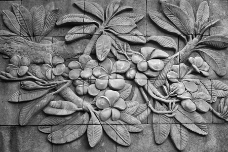 ancient philosophy: Black and white of low relief cement Thai style handcraft of plumeria or frangipani flowers on wall.
