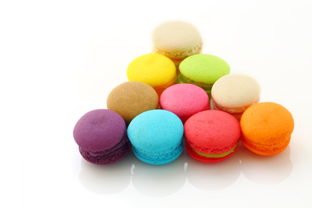 Row of colorful macarons on white background.