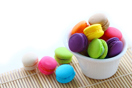 horizental: Colorful macarons in white cup on white background.