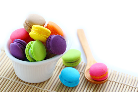 horizental: Colorful macarons in white cup with wooden spoon on white background. Stock Photo