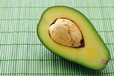 matt: Fresh of half avocado on green bamboo matt background.