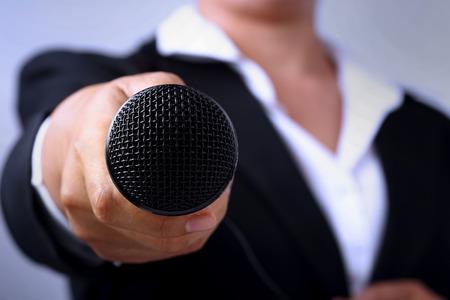 ジャーナリストは、音声マイクとのインタビューのための概念を身振りで示すことの手を作るします。