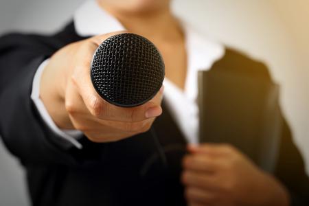 Empresaria que hace discurso con el micrófono y el concepto que gesticula de la mano para explicar la entrevista. Foto de archivo