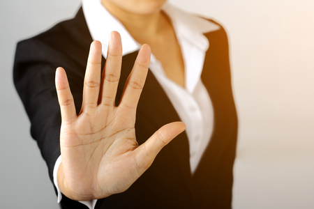 Prohibition symbol. Serious business woman shows stop sign talk to hand gesture on gray blackground. Stock Photo