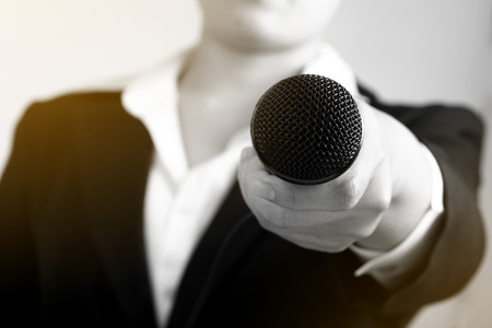 Interviewer making speech with microphone and hand gesturing concept for explaining interview, selective focus. Stock Photo