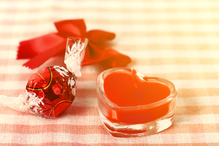 Red candle in glass with candy and knot over fabric Stock Photo