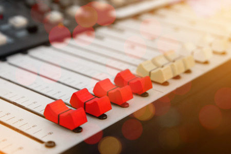 adjuster: Close up of red audio sound mixer and buttons with bokeh background.