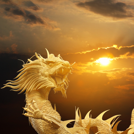 speculative: Golden chinese dragon on dramatic sky at sunset.