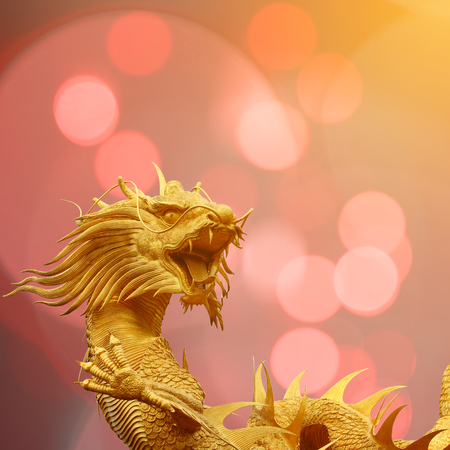 speculative: Golden chinese dragon statue with blurry bokeh background.