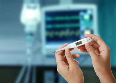 Close up of thermometer showing high temperature in woman hands with drop of saline solution and medical monitors blurred background, Temperature measuring by a thermometer, Fever measuring.