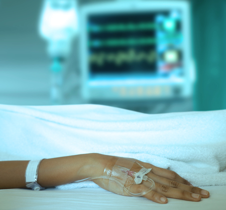 Patients hand and iv solution set and drop of saline solution with medical monitors blur background. Stock Photo