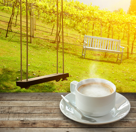 Hot coffee and smoke in white cup over wood with spoon on nature background. Stock Photo