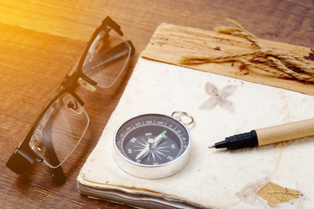 Old vintage retro compass with a book and glasses on wooden background, Travel concept background.