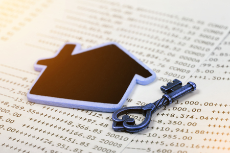 Old key with home model on account book background for finance, Concept of real estate and deal. Stock Photo