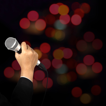 Businesswoman hand holding a microphone on blur of colorful bokeh background, seminar concept.