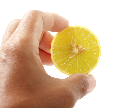Hand holding a half of lemon isolated on white background, clipping path.