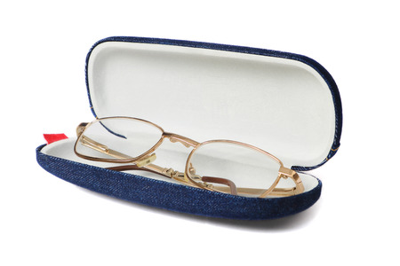 shortsighted: Gold glasses in blue opened fabric case isolated on white background. Stock Photo
